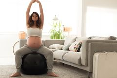 Pregnant woman doing relax exercises with a fitball. Pregnant woman doing relax exercises with a fitness pilates ball at home Stock Photos