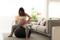 Pregnant woman doing relax exercises with a fitball. Pregnant woman doing relax exercises with a fitness pilates ball at home Stock Photo