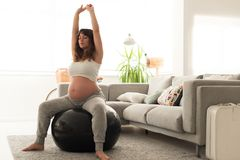 Pregnant woman doing relax exercises with a fitball. Pregnant woman doing relax exercises with a fitness pilates ball at home Stock Photography