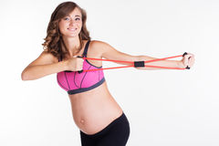 Pregnant woman doing sport with resistance band Royalty Free Stock Images