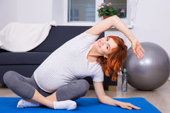 Pregnant woman doing stretching exercises at home Royalty Free Stock Photo