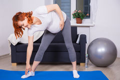 Pregnant woman doing stretching exercises in living room Stock Images