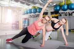 Pregnant woman doing stretching exercises with personal coach. Portrait of pregnant women doing stretching exercises with personal coach Stock Photo