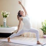 Pregnant woman doing Viparita Virabhadrasana yoga pose at home Stock Photos