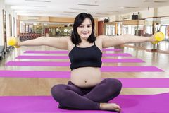 Pregnant woman doing a workout with dumbbells. Pregnant woman smiling at the camera while doing a workout with dumbbells in the fitness center royalty free stock photography