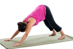 Pregnant woman doing yoga downward facing dog pose Stock Images