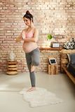 Pregnant woman exercising at home in yoga pose Royalty Free Stock Photography