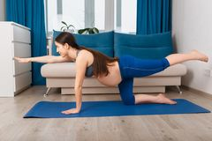Pregnant woman doing yoga exercise stock photography