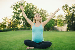 Pregnant woman doing yoga exercises on the nature Royalty Free Stock Photo