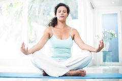 Pregnant woman doing yoga with eyes closed on exercise mat Stock Photos