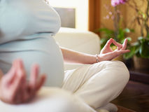 Pregnant woman doing yoga at home Stock Images