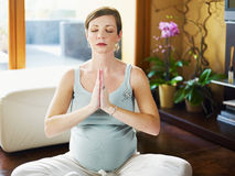 Pregnant woman doing yoga at home Royalty Free Stock Images