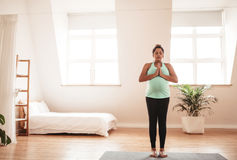 Pregnant woman doing yoga at home. Portrait of pregnant woman standing on exercise mat with her hands joined. Expectant woman doing yoga at home Royalty Free Stock Image