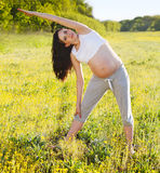 Pregnant woman doing yoga in nature outdoors Royalty Free Stock Image