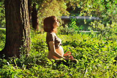 Pregnant woman doing yoga in nature. Royalty Free Stock Photos
