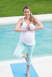 Pregnant woman doing yoga Stock Image