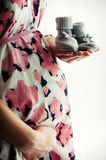 Pregnant woman in a dress holding baby`s shoes royalty free stock photo