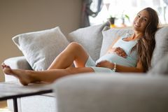 Pregnant woman in dress lying on the sofa in the living room royalty free stock images