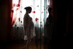 Pregnant woman in a dress. Pregnant woman standing in front of a mirror royalty free stock image
