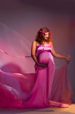 Pregnant woman dressed pink gown Royalty Free Stock Images