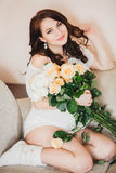 Pregnant woman dressed in a white tunic and white shoes, holding a bouquet of roses Stock Photography