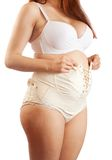 Pregnant woman dressing maternity girdle Stock Images
