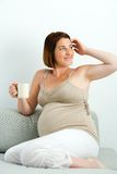 Pregnant woman drinking coffee on couch. Royalty Free Stock Images