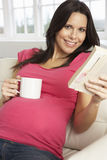 Pregnant Woman Drinking Hot Drink And Reading Book At Home Stock Images