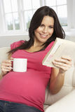 Pregnant Woman Drinking Hot Drink And Reading Book At Home Royalty Free Stock Photography