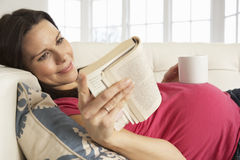 Pregnant Woman Drinking Hot Drink And Reading Book At Home Stock Photography