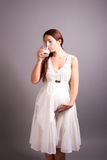 Pregnant woman drinking milk. Portrait of pregnant woman drinking milk royalty free stock image