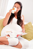 Pregnant woman drinking tea and reading magazine Royalty Free Stock Image