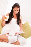 Pregnant woman drinking tea and reading magazine. Beautiful pregnant woman drinking tea and reading magazine on sofa at home Royalty Free Stock Images