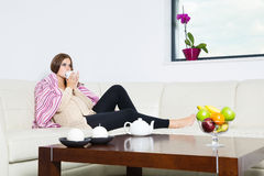 Pregnant woman drinking tea. On sofa Royalty Free Stock Image