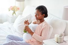 Pregnant woman drinking vegetable juice in bed Stock Photography