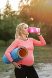 Pregnant woman drinking water after fitness. Thirsty after training expectant lady close-up, free space, sun light flare Stock Photos