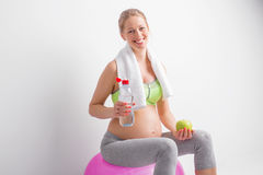 Pregnant woman drinking water after workout Royalty Free Stock Images