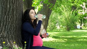 Pregnant woman drinks water from bottle