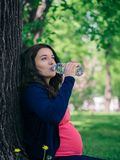 Pregnant woman drinks water from bottle. Outdoors. Copy space. Vertical Stock Photos