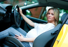 Pregnant woman driving. Pregnant woman in driving seat of the car Stock Image