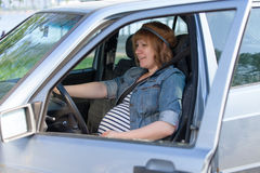 Pregnant woman in driving seat car Stock Images
