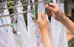 Pregnant woman dry the cloth diaper in the sun Stock Image