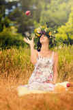 Pregnant woman in the dry grass tosses an apple Stock Photo