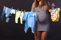 Pregnant 3. Pregnant woman drying clothes in the room Stock Photos