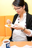 Pregnant woman eating. Cake and drinking coffee royalty free stock images