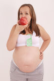 Pregnant woman eating an apple. Royalty Free Stock Image