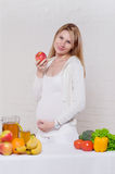 Pregnant woman eating an apple Royalty Free Stock Photos