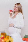 Pregnant woman eating an apple Stock Image