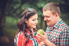 Pregnant woman eating apple with the husband outdoor Stock Image