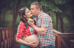 Pregnant woman eating apple with the husband outdoor Stock Images